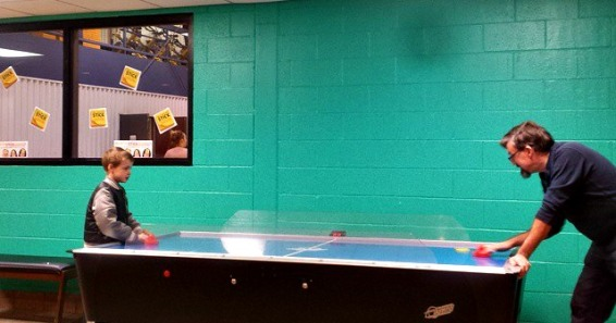 Mark and C-Dog playing air hockey at the YMCA before swim practice